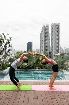 Друзья вместе на открытом воздухе практикуют позы йоги