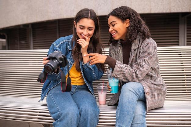 Друзья вместе на открытом воздухе с камерой и молочным коктейлем
