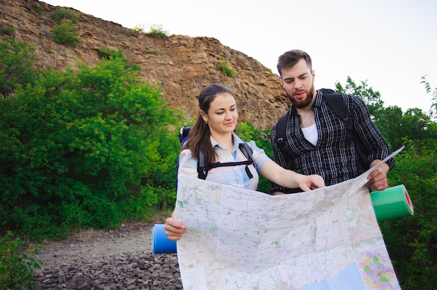 Friends travelers searching right direction on map, traveling trip together, freedom and active lifestyle concept.