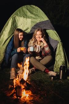 夜に焚き火の前に座っている友人の旅行者