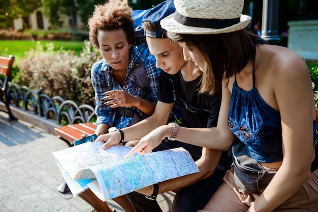Friends travelers smiling, looking route at map, sitting on bench.