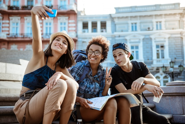 Viaggiatori di amici con zaini sorridenti, selfie, seduti vicino alla vista.