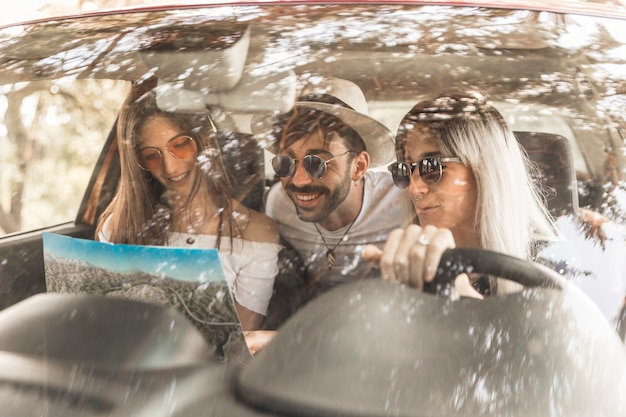 Friends travelling in car looking at map