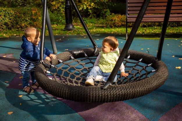 친구 두 명의 유아 소년과 소녀는 가을 공원의 놀이터에서 해먹에서 놀고 그네를 친다