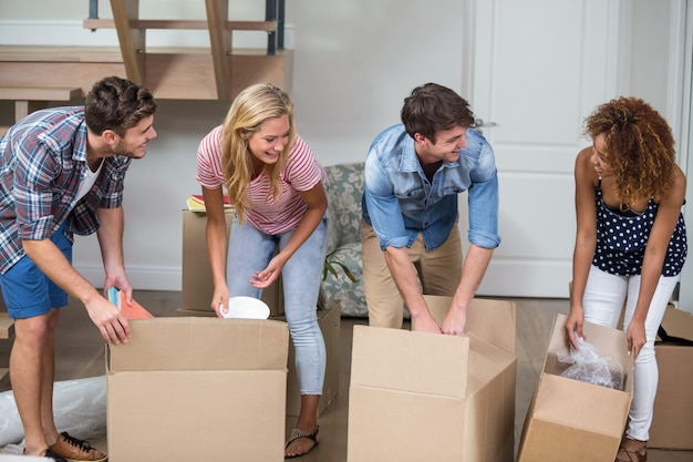 Friends unpacking carton in new house
