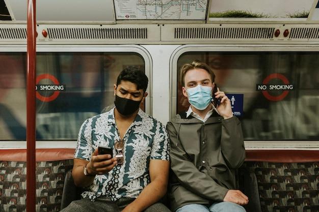 Друзья, использующие смартфон в поезде в новом нормальном состоянии