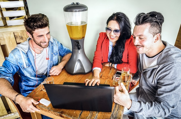 Friends using computer laptop at brewery bar