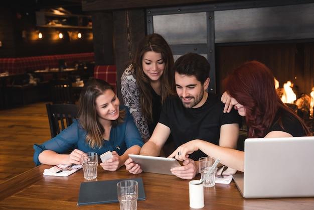 Друзья с помощью цифрового планшета в баре