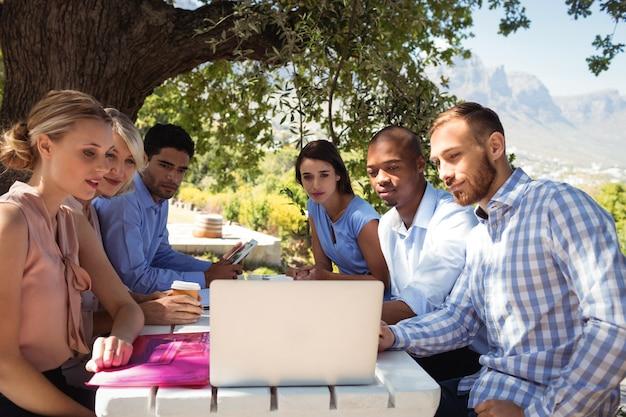 Друзья, использующие ноутбук в ресторане