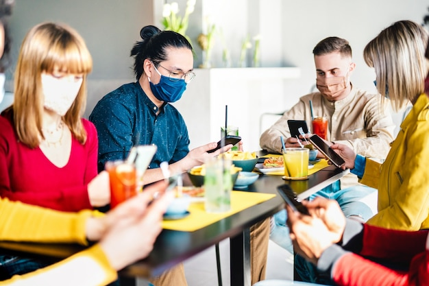 Friends using mobile phone at cocktail bar wearing face masks