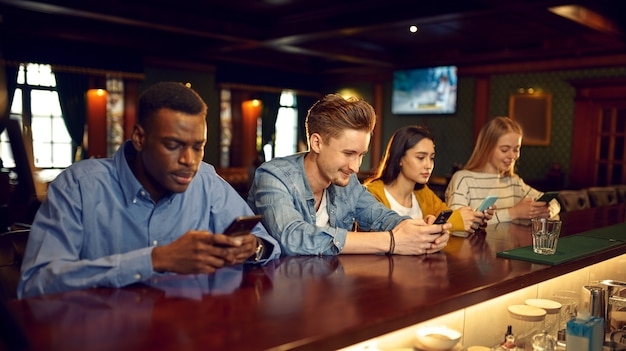 Friends using mobile phones at the counter in bar. group of people relax in pub, night lifestyle, friendship, modern realities