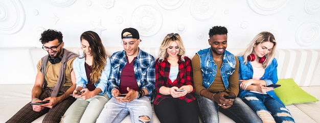 Friends using smartphone on sofa at indoor venue