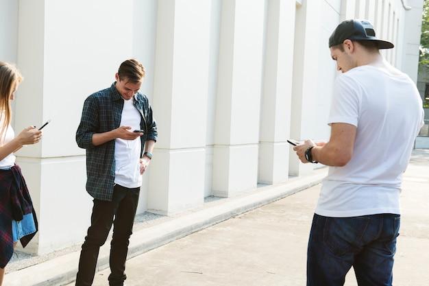 Друзья, использующие смартфоны вместе на открытом воздухе и охлаждения