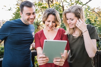 Friends using tablet near fence