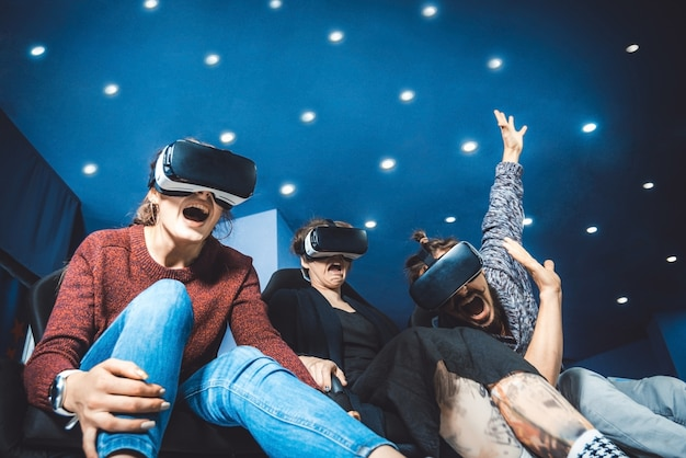 Friends in virtual glasses watching movies in the cinema with special effects in 5d