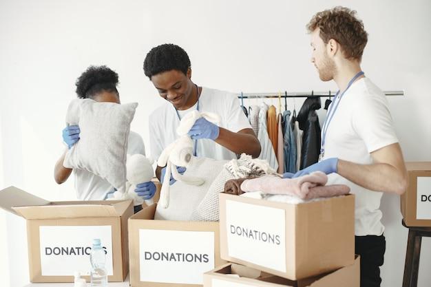 친구 자원 봉사자가 상자를 쌓습니다. 인도 주의적 지원 검사. 가난한 사람들에게 기부.