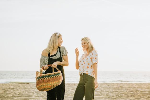 피크닉 바구니와 함께 해변에서 산책하는 친구