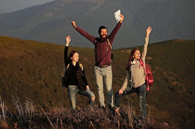 自然の山の観光客の上を歩いている友人は、かなり若いかわいい女の子や女性が笑顔で日当たりの良い自然の屋外の山の頂上に地図を持って歩いている市松模様のシャツのハンサムなひげを生やした男