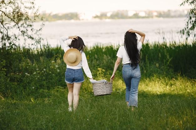 友達が歩きます。バスケットを持つ女の子。白いシャツを着た女性。