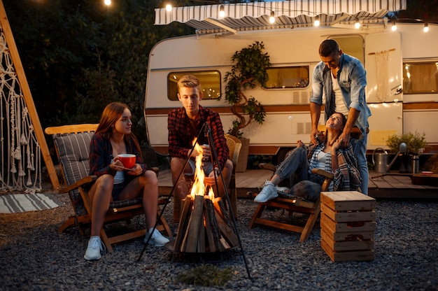 Friends warming themselves by the bonfire, picnic at camping in the forest