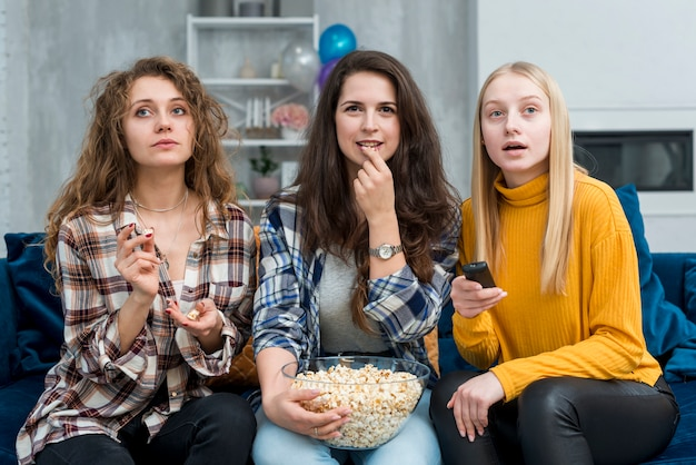 Friends watching a film while eating popcorn