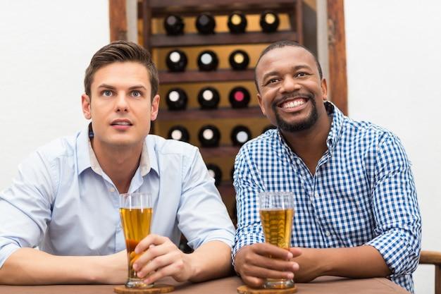 Друзья смотрят футбольный матч за пивом