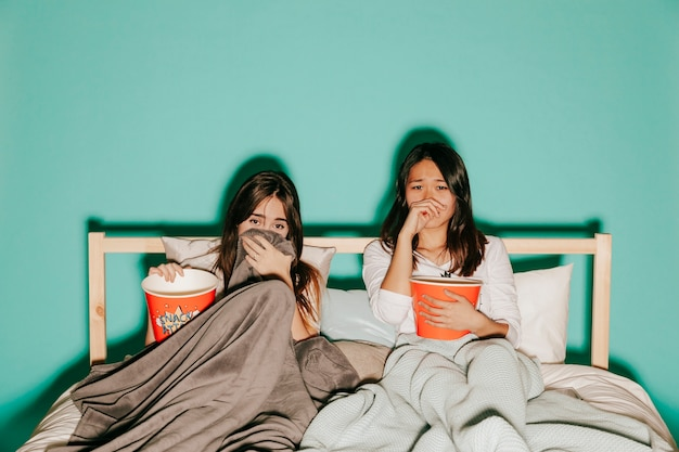 Friends watching sad movies with popcorn