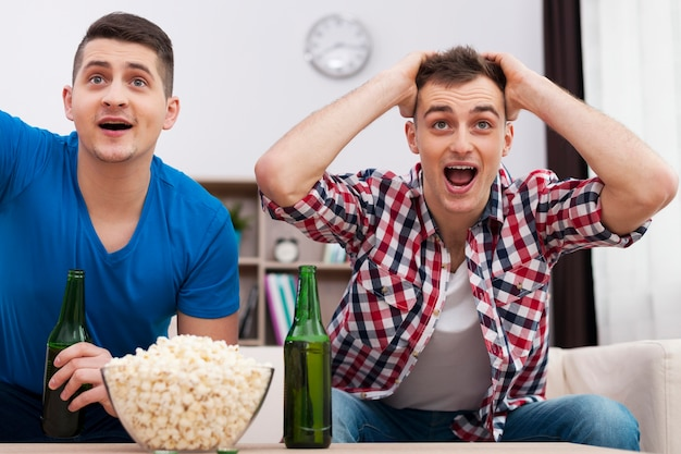 Друзья смотрят спорт по телевизору