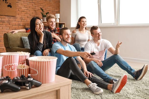 Друзья смотрят телевизор дома