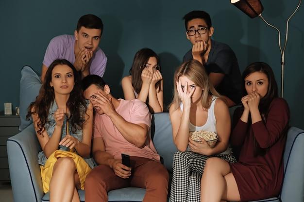 Друзья смотрят телевизор вечером дома
