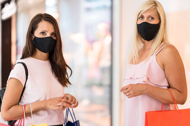 Friends wearing fabric masks in mall