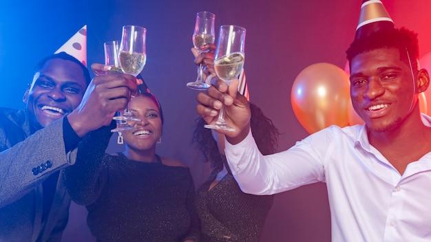 Amici che indossano cappelli da festa e tostano con champagne