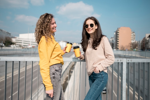 Friends wearing sunglasses holding cup of coffee