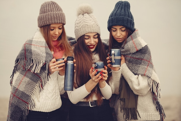 Friends in a winter park. girls in a knited hats. women with thermos and tea.