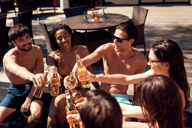 Friends with alcoholic drinks at poolside