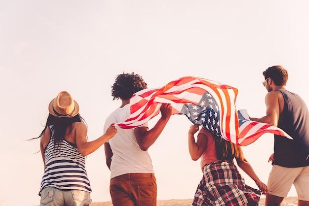 Друзья с американским флагом. вид сзади четырех молодых людей с американским флагом во время бега на открытом воздухе