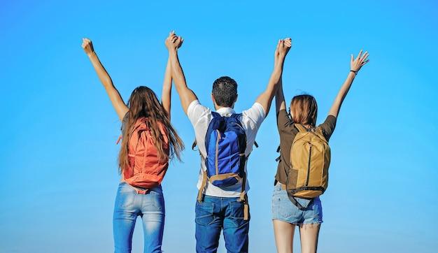 青い空に手を上げて晴れた日に屋外のバックパックと友達のんきな幸福の自由の概念自然の観光客