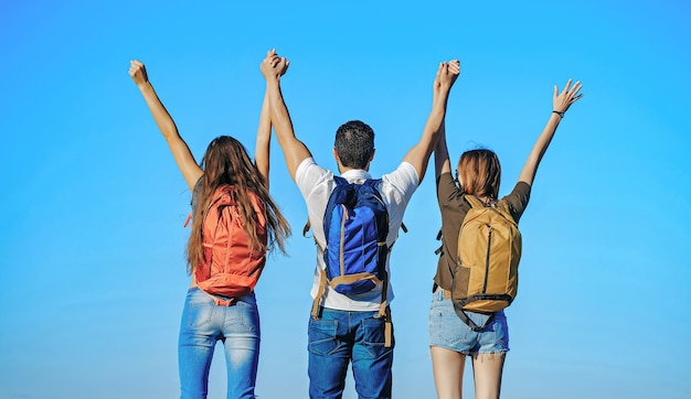 Friends with backpacks outdoor on sunny day with raised hands on blue sky  carefree happiness freedom concept tourists on nature