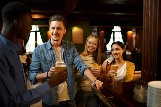 Друзья с пивом делают тост за стойкой в баре. группа людей отдыхает в пабе, ночной образ жизни, дружба, празднование события