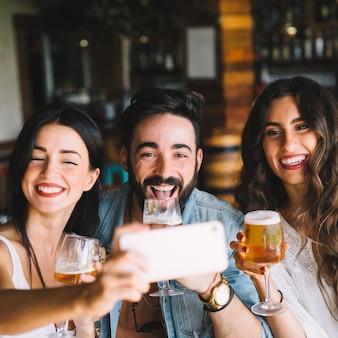 셀카를 위해 포즈를 취하는 맥주와 친구
