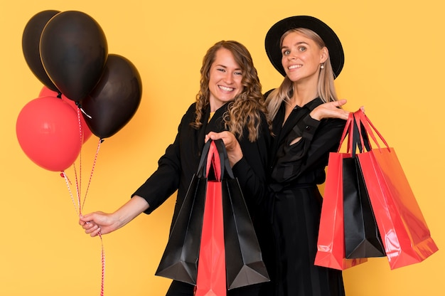 Friends with black and red bags with balloons