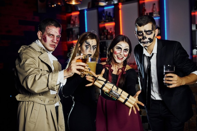 Friends with bomb in hands is on the thematic halloween party in scary makeup and costumes.