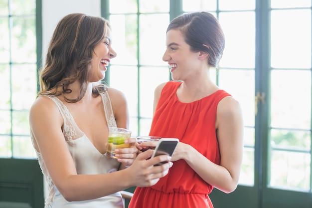 携帯電話を使用しながら笑っているカクテルグラスを持つ友人