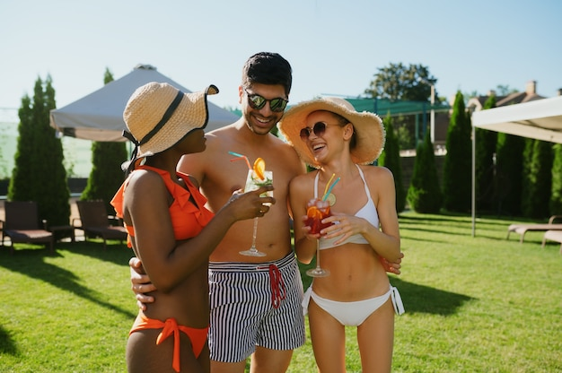 Friends with coctails pose at the pool in hotel. happy people having fun on summer vacations, holiday party at the poolside outdoors. one man and women are sunbathing