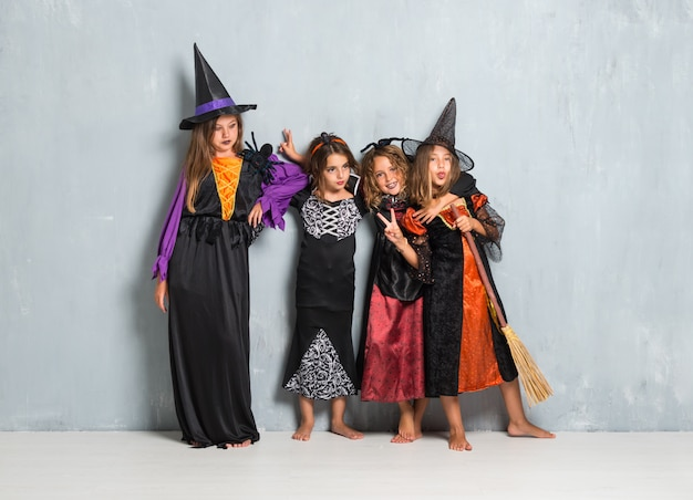 Friends with costumes of vampires and witches for halloween holidays making a joke