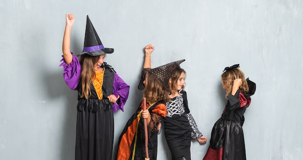 Friends with costumes of vampires and witches for halloween holidays making victory gesture