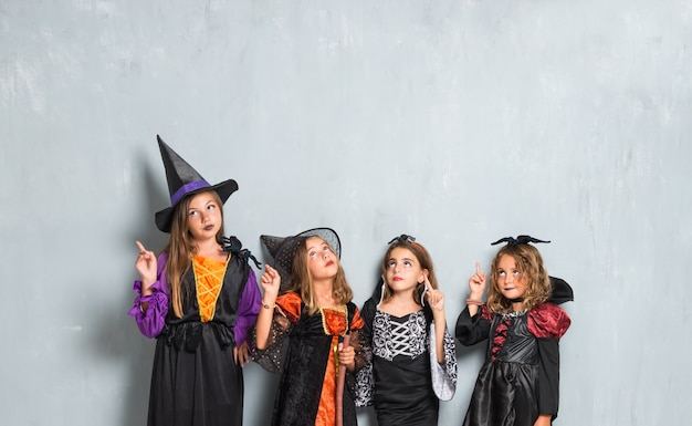 Friends with costumes of vampires and witches for halloween holidays and pointing up