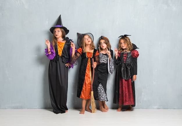 Friends with costumes of vampires and witches for halloween holidays and thinking