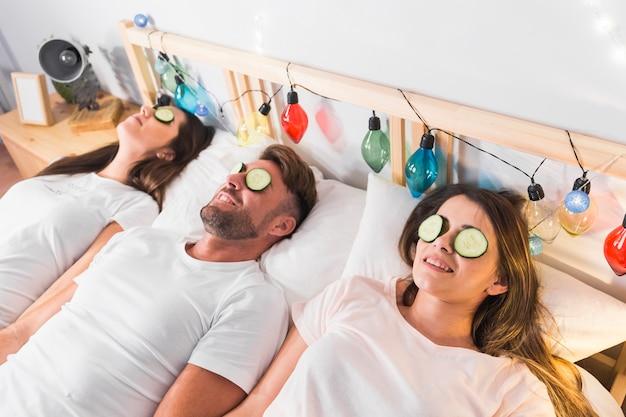Друзья с огуречным ломтиком над глазами, лежащими на украшенной кровати