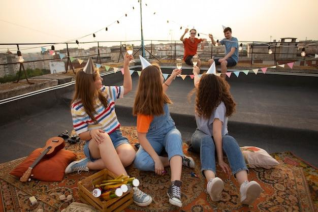 Друзья с напитками на вечеринке, полный кадр